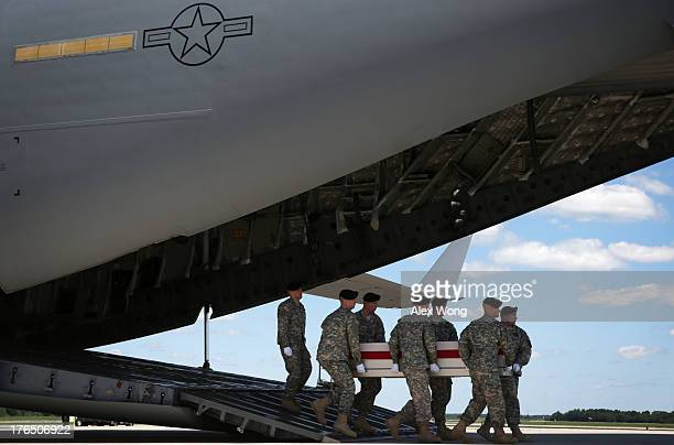 S Army carry team carries the flagdraped transfer case with the remains of Army Sergeant Jamar A Hicks of Little Rock Arkansas down the ramp of an...