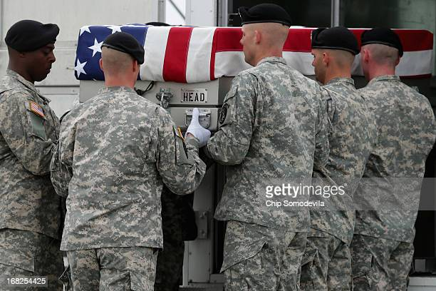 S Army carry team lifts the flagdraped transfer case with the remains of Army 1st Lt Brandon Landrum into a transfer vehicle on the tarmac at Dover...