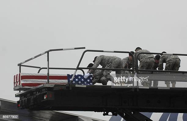 S Army carry team moves the transfer case with the remains of Army Specialist Michael Anaya of Crestview FL at Dover Air Force Base April 14 2009 in...