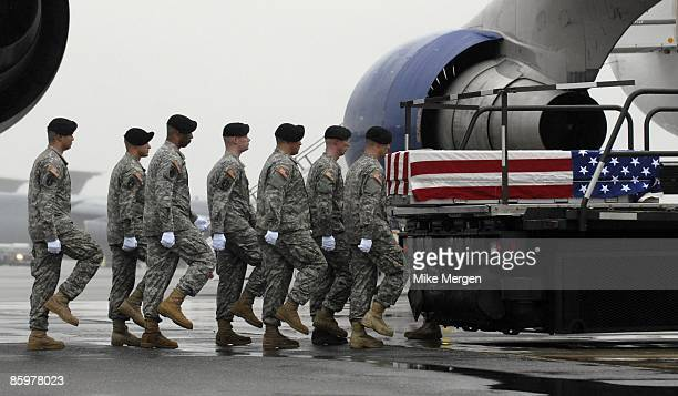 S Army carry team prepares to move the transfer case with the remains of Army Specialist Michael Anaya of Crestview FL at Dover Air Force Base April...