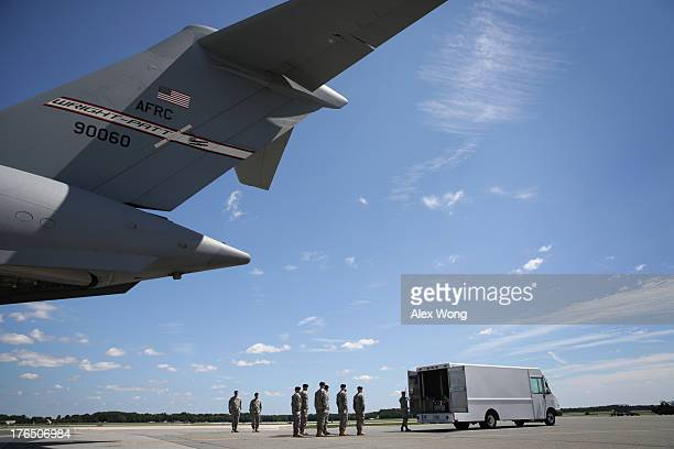 S Army carry team salutes as Air Force Senior Airman Christopher Cox closes the doors of the transfer vehicle during a dignified transfer at Dover...