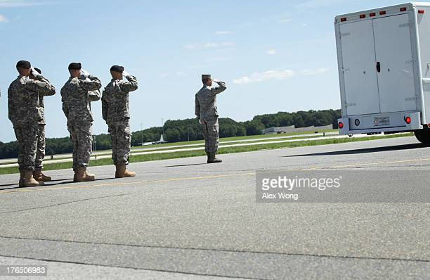 S Army carry team salutes as the transfer vehicle leaves during a dignified transfer at Dover Air Force Base August 14 2013 in Dover Delaware The...