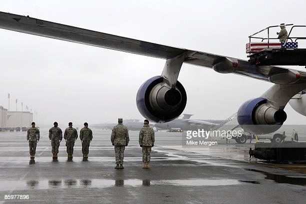 S Army carry team waits to move the transfer case with the remains of Army Specialist Michael Anaya of Crestview FL at Dover Air Force Base April 14...