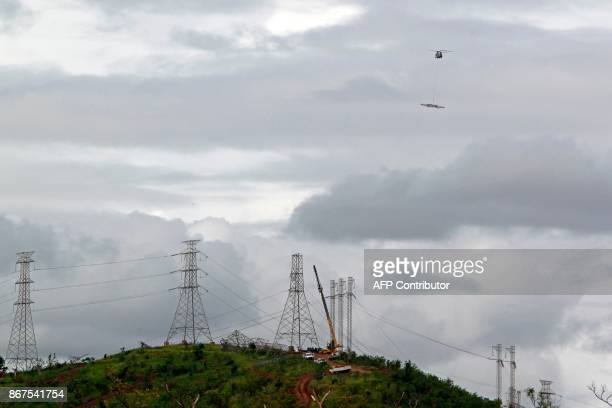 Army CH47 Chinook helicopter lifts a power transmission tower for repairs on October 28 2017 after the passing of Hurricane Maria in Guayama Puerto...