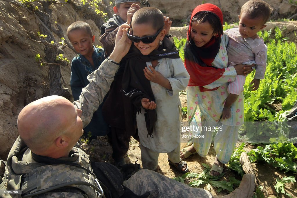 U.S. Army Chaplain Carl Subler puts his sunglasses on an Afghan boy while at an opium poppy farm on March 14, 2010 at Howz-e-Madad in Kandahar province, Afghanistan. He had accompanied soldiers from the 2nd Battalion, 1st Infantry Regiment on an offensive operation against Taliban in the area. Although U.S. military chaplains are non-combatants, CPT. Subler goes on combat patrols to provide support for troops in the field. Military chaplains travel the battlefield throughout Afghanistan, providing a backbone of support for thousands of soldiers struggling with the difficulties of war and year-long deployments away from home.