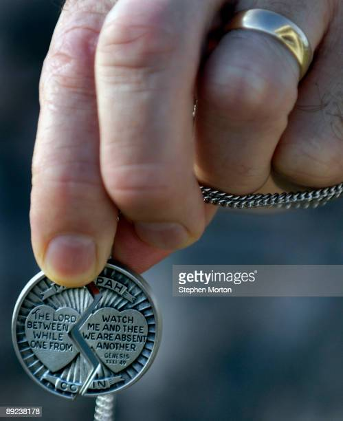 Army Chaplin holds the two halves of a pewter medallion given to soldiers and their spouses with the 293rd Military Police Company before taking part...