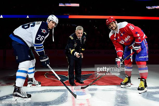 Army Chief of Staff Gen Mark Milley takes part in a ceremonial puck drop with Blake Wheeler of the Winnipeg Jets and Alex Ovechkin of the Washington...