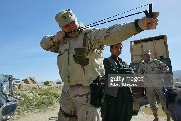 US army Civil and Humanitarian Affairs officer Sergeant Danny Eller shoots an Afghan child's sling shot during a visit to a small Karabagh area...