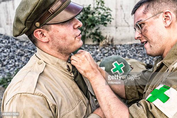 wwii us army combat medic helping officer uniform - military doctor stock photos and pictures