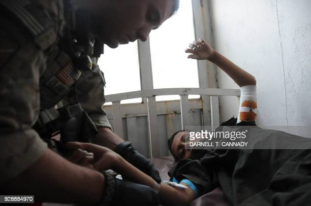 US Army Combat Medic Staff Sergeant Dennis Magnasco treats an Afghan boy who was injured in a mortar attack 2011 in Ghazni Afghanistan A group of US...