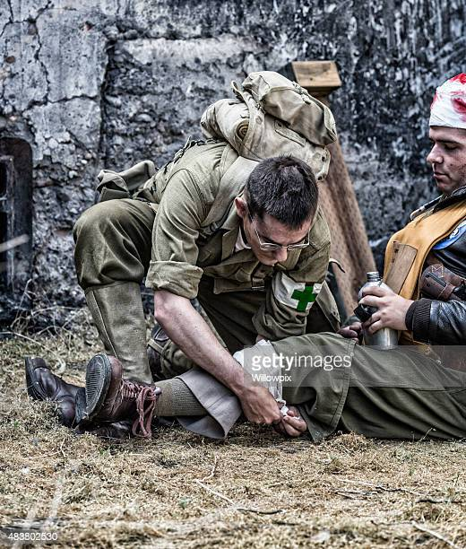 wwii us army combat medic treating wounded usaac officer - military doctor stock photos and pictures