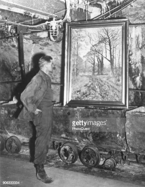 US Army Corporal Donald Ornitz looks at an unidentified painting in the Merkers salt mine where it had been stored after Nazis stole it during World...
