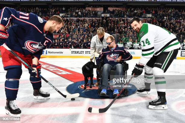Army Corporal Josh Sommers accompanied by his mother Lisa Hopkins and service dog Debra drops the ceremonial first puck for Nick Foligno of the...
