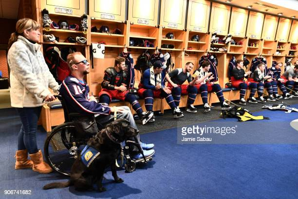 Army Corporal Josh Sommers accompanied by his mother Lisa Hopkins and service dog Debra listen as Nick Foligno of the Columbus Blue Jackets reads off...