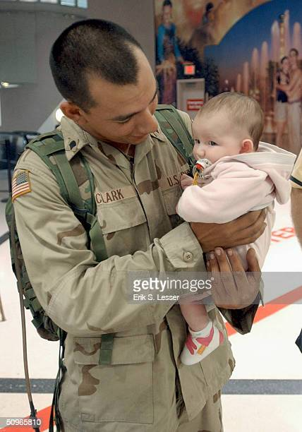S Army Cpl Andrew Clark holds his 3monthold daughter Alisha for the first time upon his arrival at Hartsfield Jackson International Airport June 16...