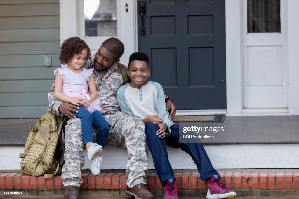 Army dad talks with his kids before his deployment : Stock Photo