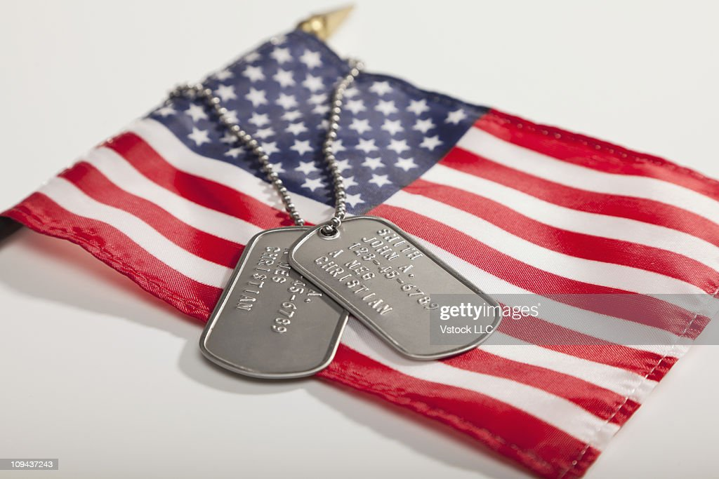 Army dog tags on Stars and Stripes flag : Stock Photo