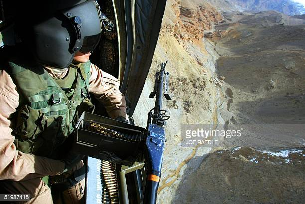 Army door gunner Sgt Jeff Bierman from Alton Illinois flies 17 March 2002 over eastern Afghanistan in a Chinook helicopter The helicopter was...
