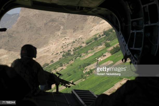 Army flight engineer mans a machine gun as a Chinook CH-47 helicopter lands on a resupply flight for the 10th Mountain Division's Forward Operating...