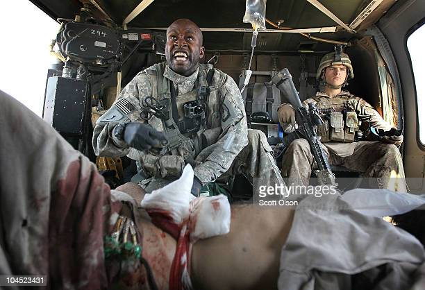 Army flight medic SGT Tyrone Jordan of Charlotte, North Carolina, from Dustoff Task Force Shadow from the 101st Combat Aviation Brigade gives first...