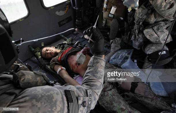 Army flight medics from Charlie Co. Sixth Battalion, 101st Airborne Combat Aviation Brigade, Task Force Shadow, tend to a wounded Afghan National...