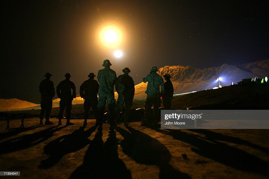 U.S. Army forward observers watch as an illumination round from an American 81mm mortar lights up the mountains near their outpost at Deh Afghan June 29, 2006 in the Zabul Province of southern Afghanistan. American forces are the main element of some 10,000 coalition troops finishing the second week of Operation Mountain Thrust aimed at rooting out Taliban fighters across southern Afghanistan.