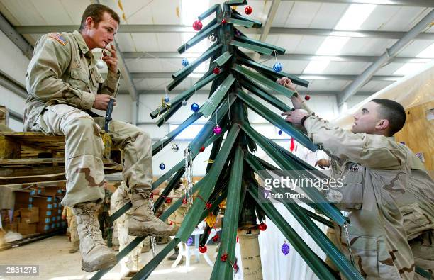 Army Fourth Infantry Division Sgt Robert Scott of Colorado Springs Colorado and Lt James Micheletti of Billings Montana prepare a makeshift Christmas...