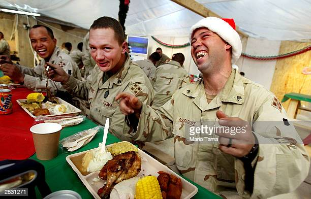 Army Fourth Infantry Division soldiers Sgt Kelvin Rodriguez Sgt John Thornburg and Sgt Arthur Aquino share a laugh during Christmas dinner December...