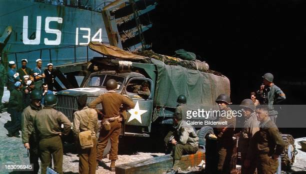 A US Army GMC truck embarking on a landing ship tank at Portland Harbour Devon for the invasion of Normandy June 1944 GIs and others are watching...