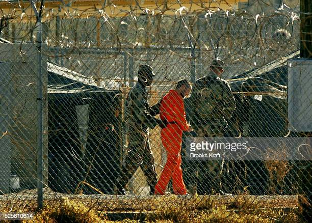 US Army guards escort a detainee at Camp Xray where Taliban and Al Quada detainees are being held The detention center is a temporary holding...