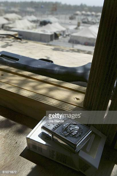 S Army guards lighter and shotgun sit in his guard tower as he keeps an eye on prisoners that are housed in tents in the Abu Ghraib prison on July 15...