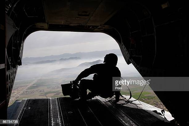 S army gunner sits at the rear of a CH47 helicopter as he escorts the blackhawk helicopter carrying US Secretary of Defense Robert Gates enroute from...