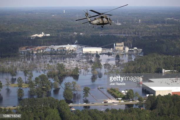 Army helicopter carrying Lt. Gen. Jeffrey S. Buchanan, U.S. Army North Commanding General., flies over homes and businesses flooded by heavy rains...