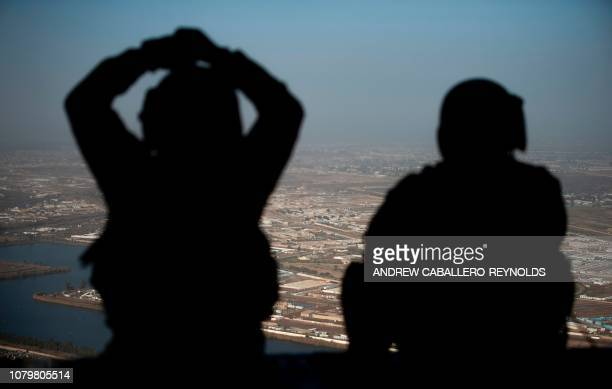 Army helicopter crew members look out of their Chinook helicopter as they fly from the US Embassy to Baghdad International airport, following the...