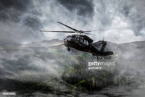 Army Helicopter Flies over Foggy Mountains