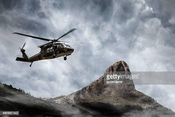 Helicóptero militar vuela más de niebla las montañas
