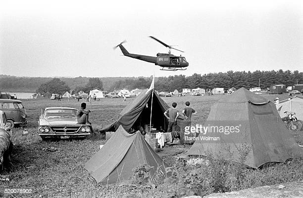 Army helicopter flies over the camping area at the Woodstock Music Art Fair Bethel NY August 15 1969