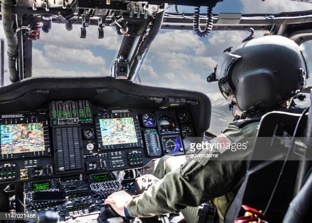 army helicopter pilot riding helicopter - helicopter stock pictures, royalty-free photos & images