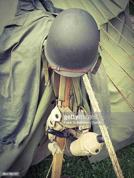 Army Helmet On Wooden Post Beside Tent