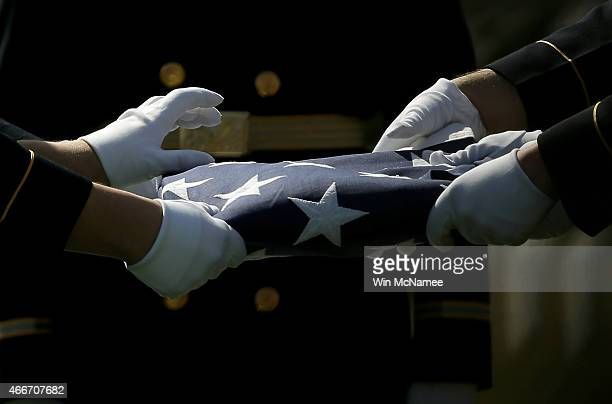 S Army honor guard folds an American flag that covered a casket with the remains of eight airmen who were listed as missing in action during a burial...