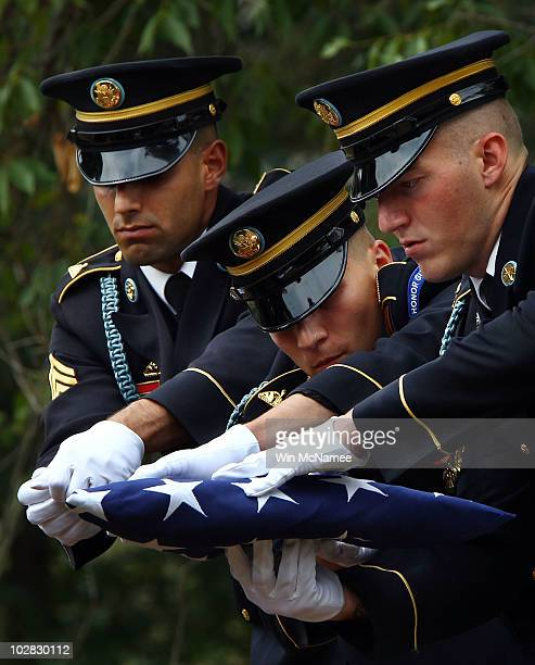 S Army honor guard team passes the folded American flag that covered the casket of World War I casualty Private First Class Thomas D Costello during...