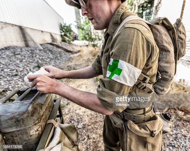 wwii us army infantry medic soldier preparing medical bandage - arm band stock pictures, royalty-free photos & images