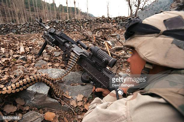 A US Army infantryman guards the perimeter while others search a Pashtun village on the border with Pakistan