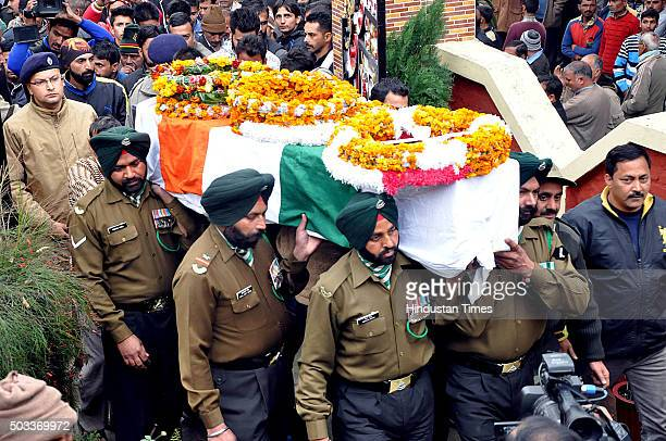 Army jawans and officers carry the coffin of martyr Sanjeevan Singh Rana who was killed in terrorist attack in Pathankot during his cremation at his...