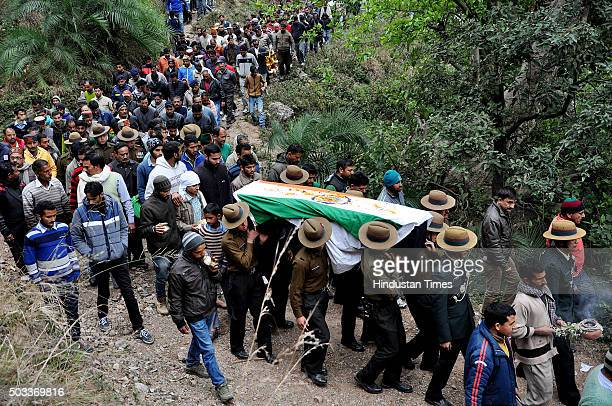 Army jawans and officers carry the coffin of soldier Havildar Jagdish Chand who was killed in terrorist attack in Pathankot followed by villagers...