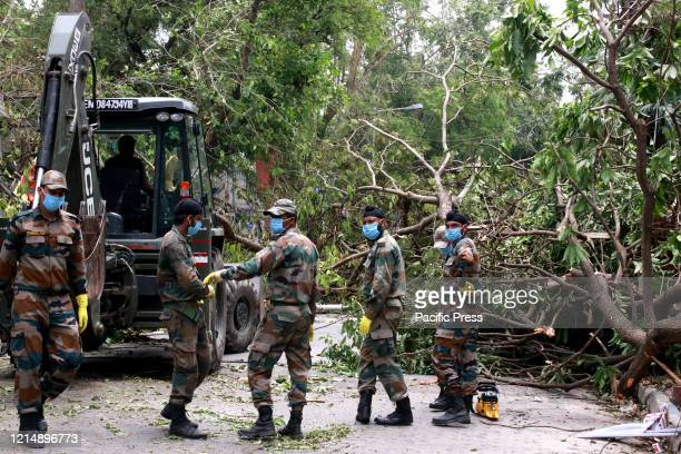 Army Jawans work to clear uprooted tree from a road after Cyclone Amphan hit the region in Kolkata A powerful cyclone ripped through densely...