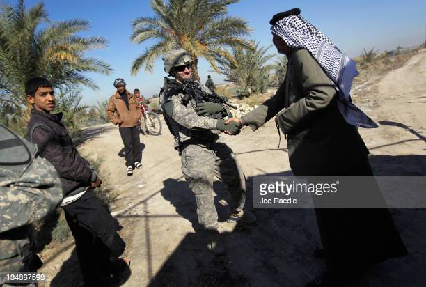 S Army Lieutenant Adam Wilson from Ontario California of the 282 Field Artillery 3rd Brigade 1st Cavalry Division shakes hands with Sheik Mahmood...