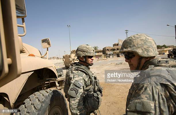 Army Lt Col Michael Pembrick center of 3rd Brigade Combat Team 4th ID waits to speak with an Iraqi Army soldier about possible nearby roadside bombs...