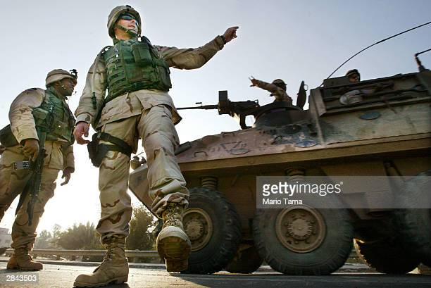 S Army Lt Dave Devin of Vincennes Indiana waves to a passing Australian armored personnel carrier while guarding a checkpoint as Spc William McCoy of...