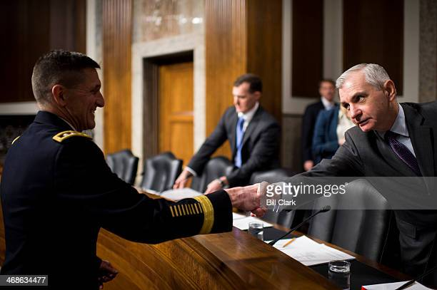 Army Lt Gen Michael Flynn director of the Defense Intelligence Agency left shakes hands with Sen Jack Reed DRI before the start of the Senate Armed...